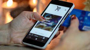 スマートフォンでウェブショップのカード支払いをする女性